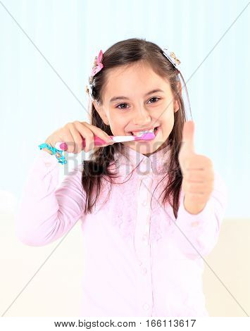 beautiful little girl brushing her teeth with a toothbrush.photo has a empty space for your text