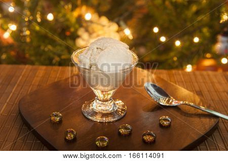 Bowl of ice cream with a Christmas tree in the background