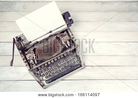 Dirty vintage tapewriter on white wooden table with copy space