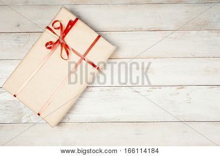 Wrapped gift box with red ribbon on white wooden table with copy space