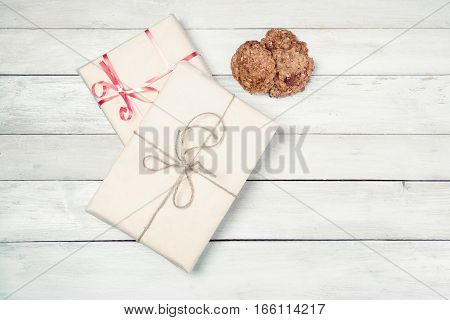 Two wrapped gift boxes and home made cookies on white wooden table