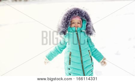 Pretty little girl in winter park. She is happy. Outdoor Activities. Close-up portrait