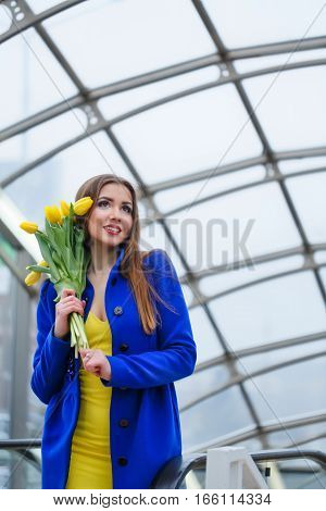 Young attractive girl in a blue coat and yellow dress holding a bouquet of yellow tulips. Spring is coming to town. She holds flower in the head