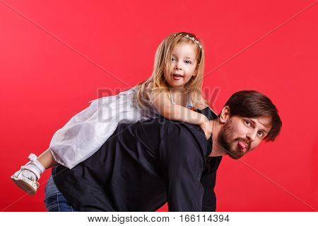 Father and daughter piggyback. They show tongues. Emotional games with your child. Family fun. The joy of communication. Parental support.