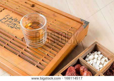 Chinese Herbal Medicine with a cup of tea on table.