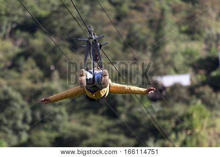 July 15, 2016 Banos, Ecuador: a man slides head first on zip-line across a canyon