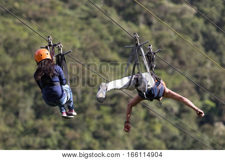 July 15 2016 Banos Ecuador: a man and a woman slides in tandem on zip-line across a canyon