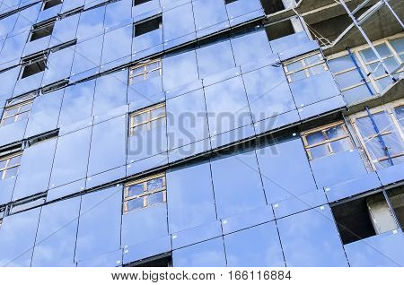 Facing a blue glass wall with reflections of sky building