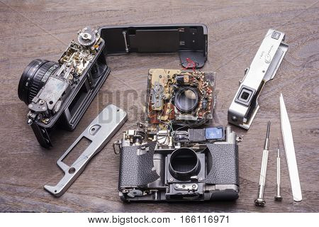 Decomposed of two old rangefinder film camera on wood table