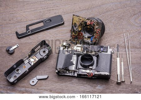 Decomposed of an old rangefinder film camera on wood table