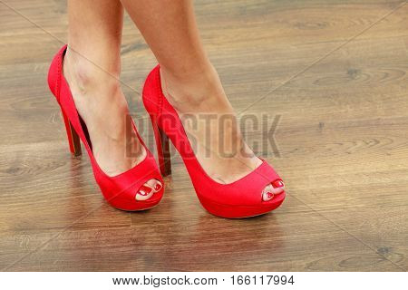 Female fashion. Closeup red high heels spiked fashionable shoes on female legs