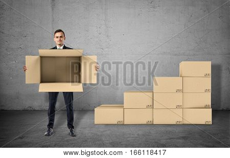 Businessman is showing an open box in his hands staying on gray background. Making money. Transport and logistics. Business management
