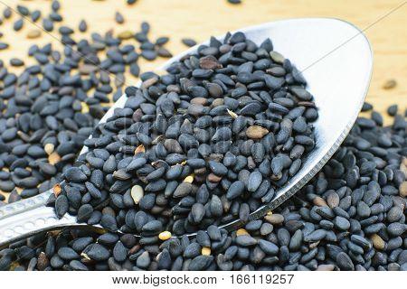 Black sesame seeds. Healthy sesame seeds in spoon on wooden table