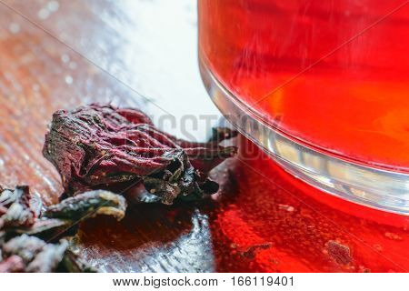 Closeup of roselle with drink over wooden surface