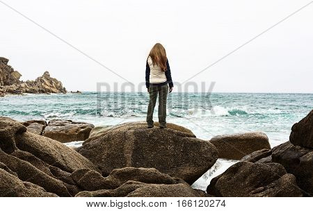 Lonely girl standing on rock. Sad woman