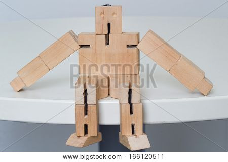 Wooden Robot Toy sitting at white table