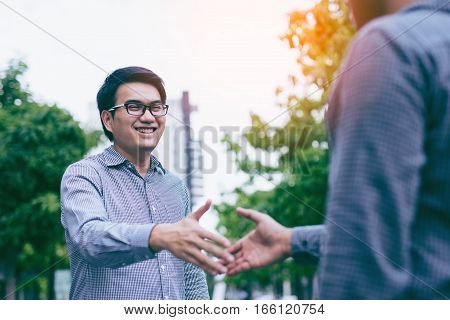 Men shaking hands. Sealing a deal! Two happy young asian businessman shaking hands while standing on the paving tiles cement brick floor.