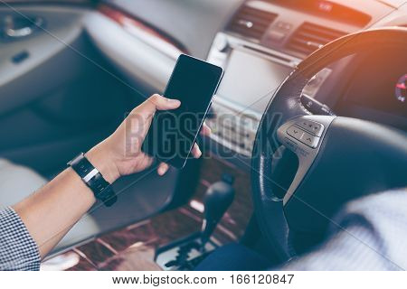 Hand's man using smartphone while driving the car (selective focus) - transportation and vehicle concept