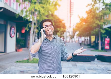 Young Asian Handsome Businessman Happy Smiling While Reading His Smartphone