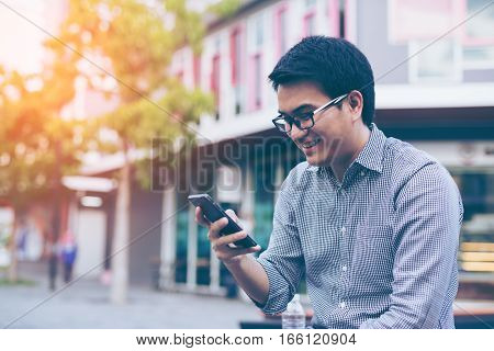 Young Asian Handsome Businessman Smiling While Reading His Smartphone