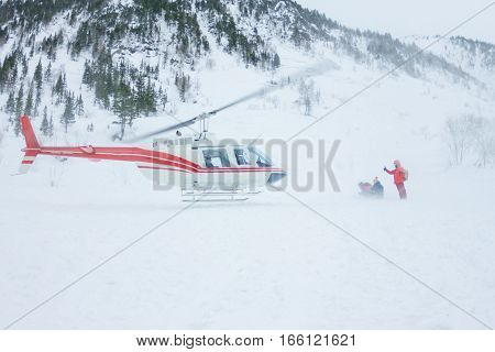 The helicopter landed people in the mountains in winter raising a cloud of snow.