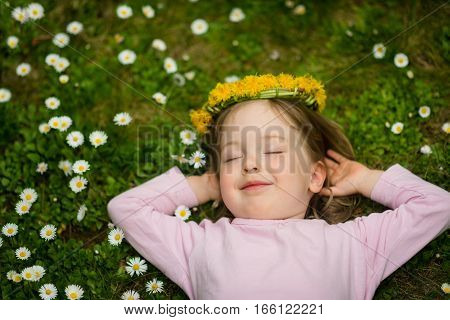 Little girl with dandelion wreath daydreaming in grass full of daisy flowers