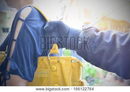 Hand of bandit steal bag another person in the public under the sunlight