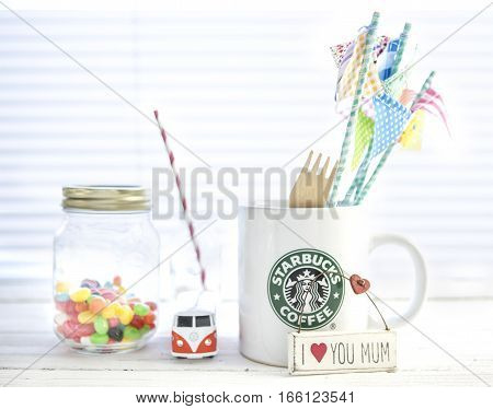SWINDON UK - JANUARY 20 2017: White Starbucks Mug with Starbucks logo VW camper Van Jelly beans on a White wood Background.