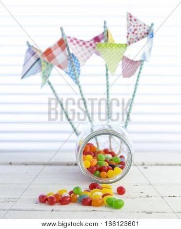 Colorful jellybeans spilling from a Jar with white rustic background