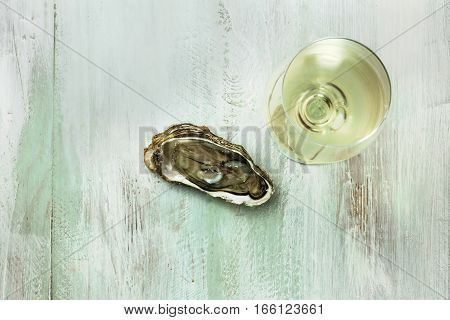 An overhead photo of a freshly opened oyster and a glass of white wine, on a wooden background texture with copyspace