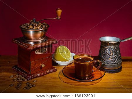 Coffee in the Cup. The foam not next to opal lemon and manual coffee grinder. Claret background.