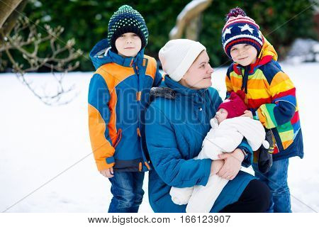 Happy mother holding newborn baby girl on arm after birth. Two little sons by mum and sister. family going from hospital to home. New born child sleeping. Outdoors, winter and snow.