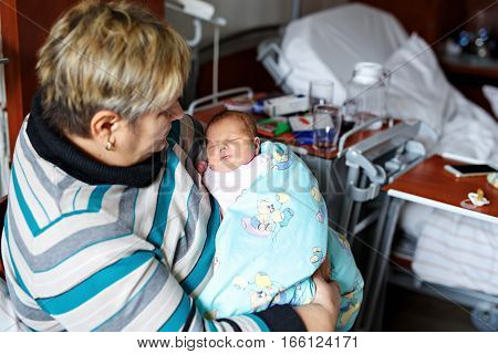 Happy grandmother holding newborn baby grandchild on arms in hospital. Proud senior woman with cute little girl. Family, love, grandparents, carefree childhood.