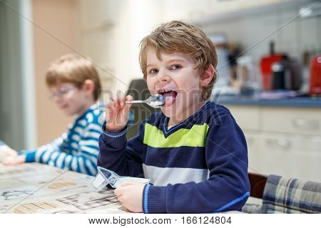 Adorable little school boy eating yogurt indoor. Blond child in domestic kitchen or in school canteen Cute kid and unhealthy sweet food