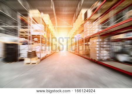 Large industrial warehouse. Long shelves with a variety of boxes and containers. The effect of motion blur. Bright sunlight.
