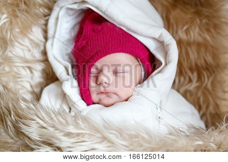 Portrait of sleeping newborn baby in warm winter clothes. Beautiful cute girl in warm overall, cap. Peaceful child sleep during outdoor walk.