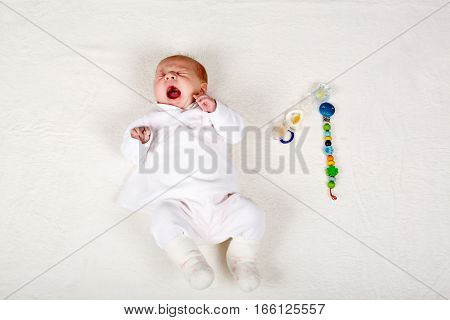 Cute adorable newborn baby girl one month old crying or yawning . New born child, little girl with toy and pacifier dummy as nomber one. Family, new life, childhood, beginning concept.