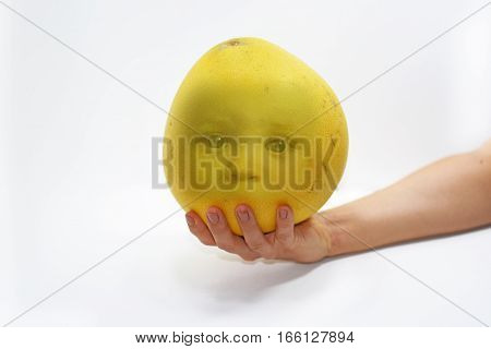 Woman hand with big yellow Pomelo on baby face on it. Isolated on white background.