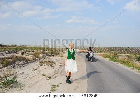 stylish girl stops the biker on the road