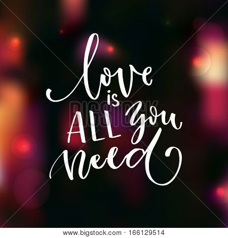 Love is all you need. Romantic saying for Valentine's day card. Modern calligraphy handwritten on blurred background with lights and bokeh