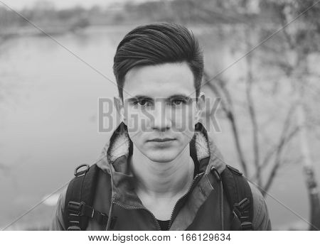 Black and white portrait of the young man on the city river