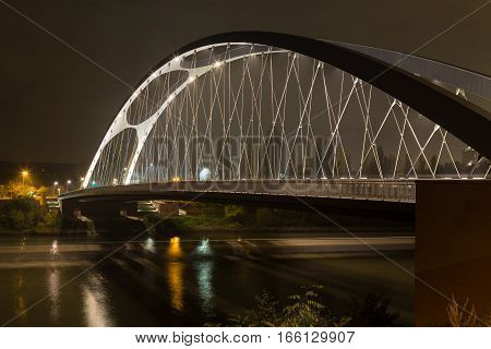 Modern bridge over the river Main lit by lamps at night. Frankfurt am Main . Germany.