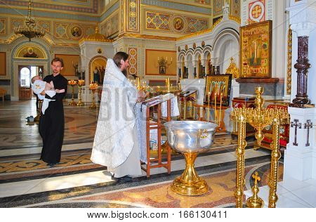 The priest performs the rite of baptism of an infant in the Christian Orthodox Church. Crimea, Sevastopol. August 22, 2009
