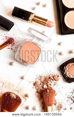 crushed decorative cosmetics nude on white background top view.