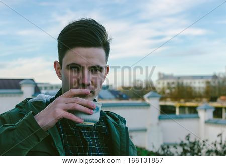Young man and cup with coffee on the city street in autumn time