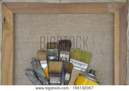 Brushes tubes of paint and yellow balloon lying on a stretcher with canvas