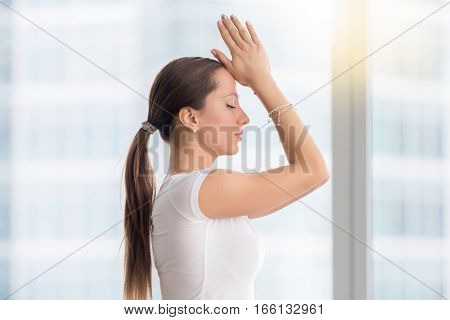 Young attractive yogi model practicing yoga exercise, working out with closed eyes, wearing sportswear, white t-shirt, indoor, near window with city view, closeup Side view lifestyle portrait