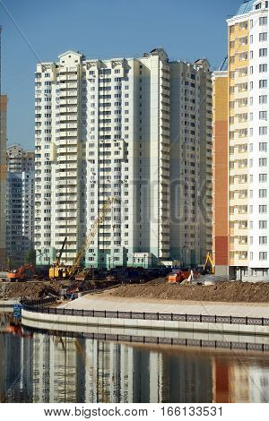 Cityscape with new modern buildings construction near river over clear blue cloudless sky in summer day, vertical photo