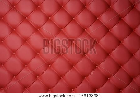 Red leather carriage upholstery as a background.
