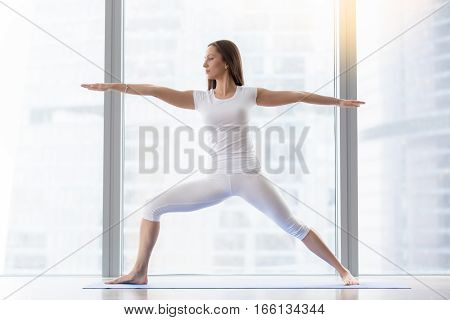 Young attractive woman practicing yoga, standing in Warrior two exercise, Virabhadrasana II pose, working out, wearing sportswear, white t-shirt, pants, indoor full length, floor window with city view